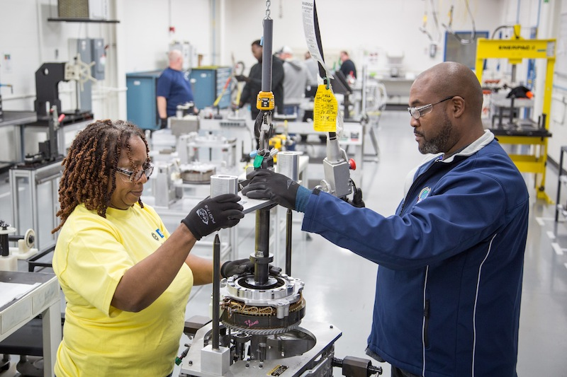 Chevrolet Volt drive unit manufacturing launch team members Aretha Lee (left) and Patrick Sled install an electric motor into an all-new Volt drive unit case housing Monday, October 20, 2014 at the General Motor's Powertrain plant in Warren, Michigan. The two-motor drive unit operates approximately 5-12 percent more efficiently and weighs 100 lbs. (45 kg) less than the current system. (Photo by Jeffrey Sauger for Chevrolet)